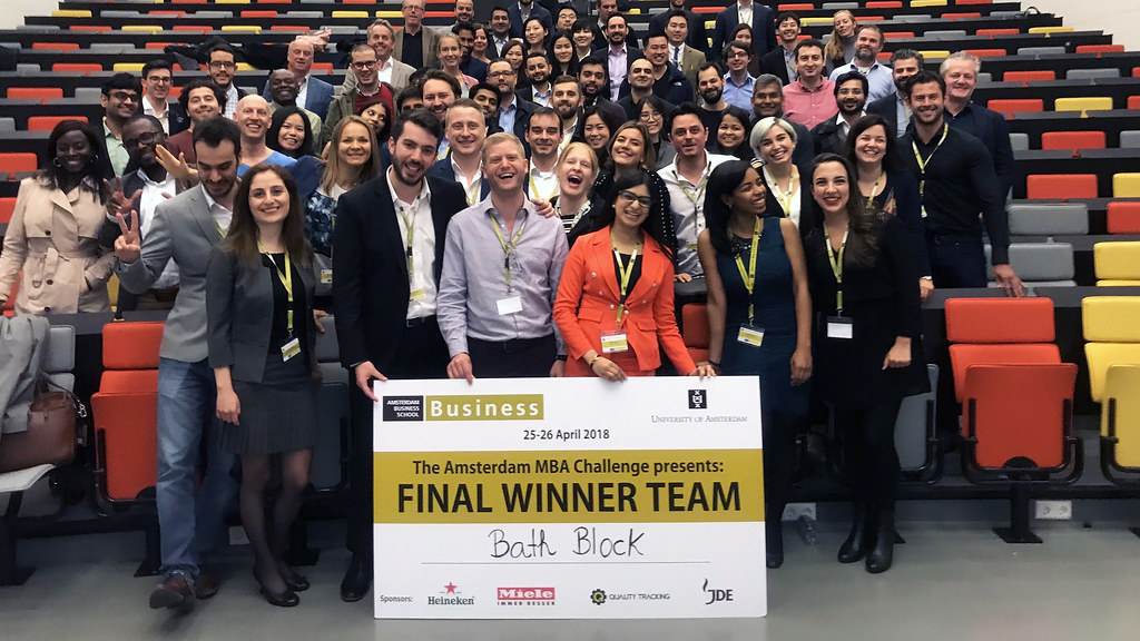 A group of people posing in a large room with a winners' placard.