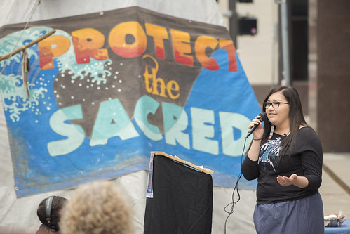 photo of a woman speaking outdoors, sign behind with words, protect the sacred