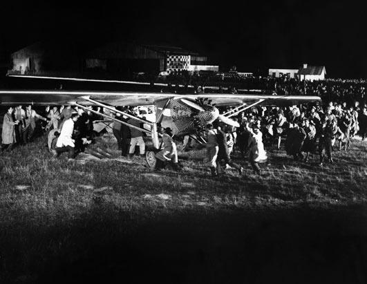 Bringing his plane to a stop after landing, Charles Lindbergh open his cabin door and was immediately dragged from the cockpit by the enthusiastic crowd who then carried him upon their shoulders for