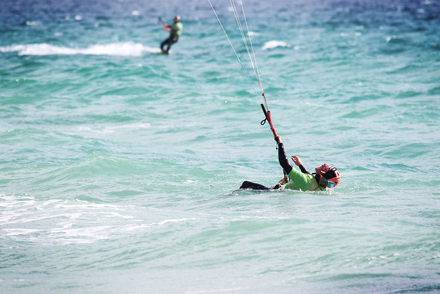 A man lying in the water on his back trying to get up on a kite. Kitesurfing lessons in Tarifa, Spain