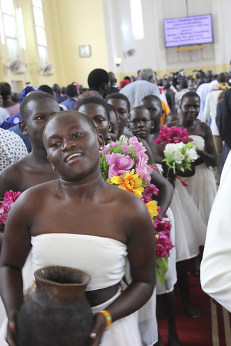 Young girls dance and drop flower petals as the offertory is taken