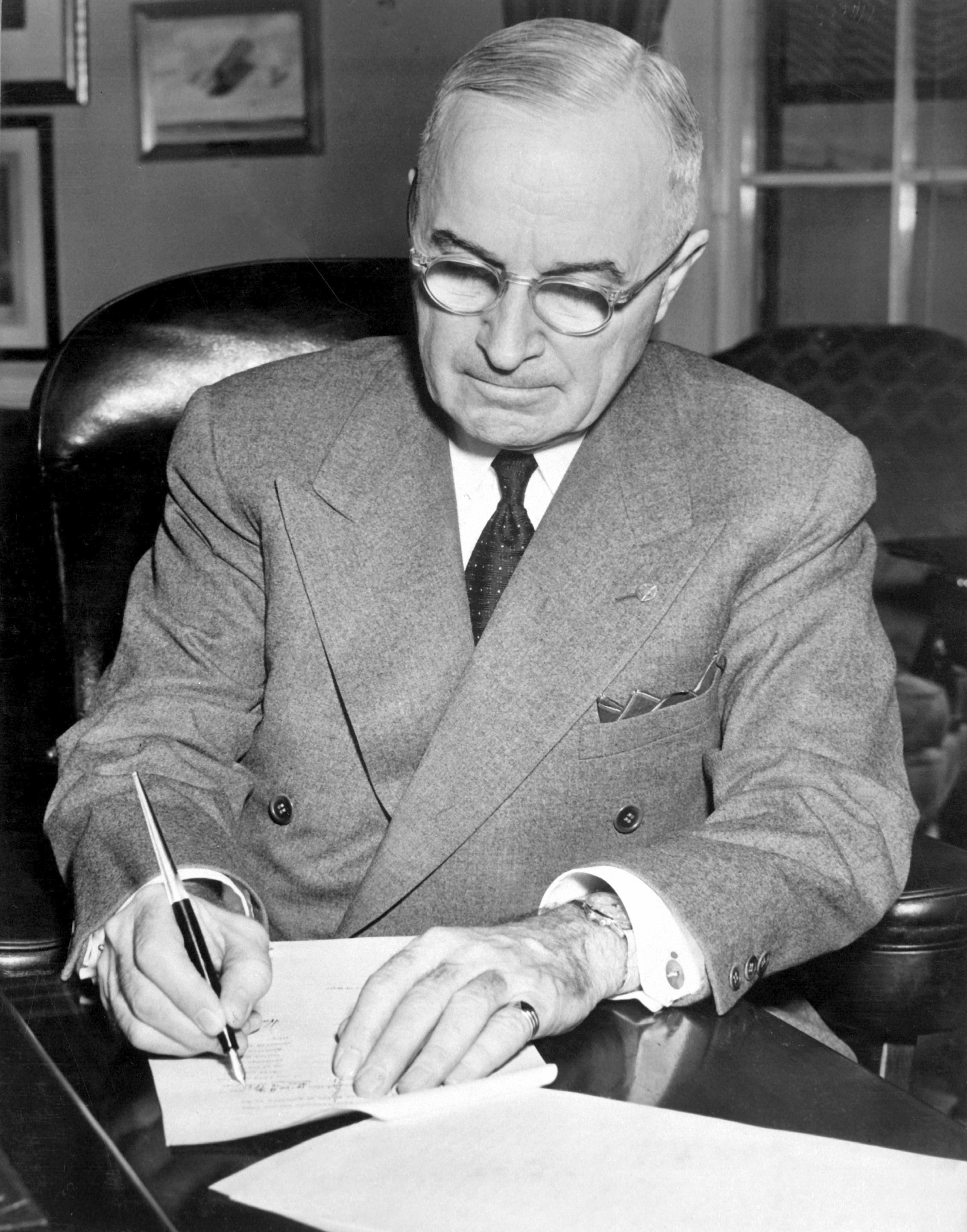 President Harry S. Truman is shown at his desk at the White House signing a proclamation declaring a national emergency and authorizing U.S. entry into the Korean War on December 16, 1950. Photo from the National Archives and Records Administration, cataloged under the National Archives Identifier (NAID) 541951.