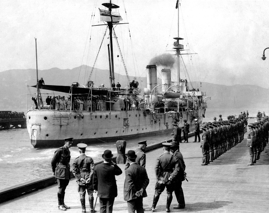 HMS Philomel berthing at Queen's Wharf, Wellington, on March 16, 1917, after returning from wartime service overseas. When the ship docked for maintenance in Bombay earlier that year, it was discovered that major repairs were needed to its deck and hull. Rather than undertake this expensive work, the Royal Navy detached the ship from its fleet and sent it back to New Zealand. A guard of 50 corporals from the New Zealand Expeditionary Force, as well as several VIPs, greeted New Zealand's first warship when it arrived in Wellington. Once back in New Zealand waters, Philomel served as a stationary depot ship then as a training and accommodation facility at Devonport naval base, Auckland.