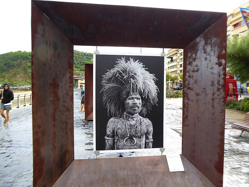 Juxtaposed sculptures in San Sebastian on the north coast of Spain, where a Melanesian warrior is framed in a core 10 steel picture frame , and is of interest for travellers who like themed travel.