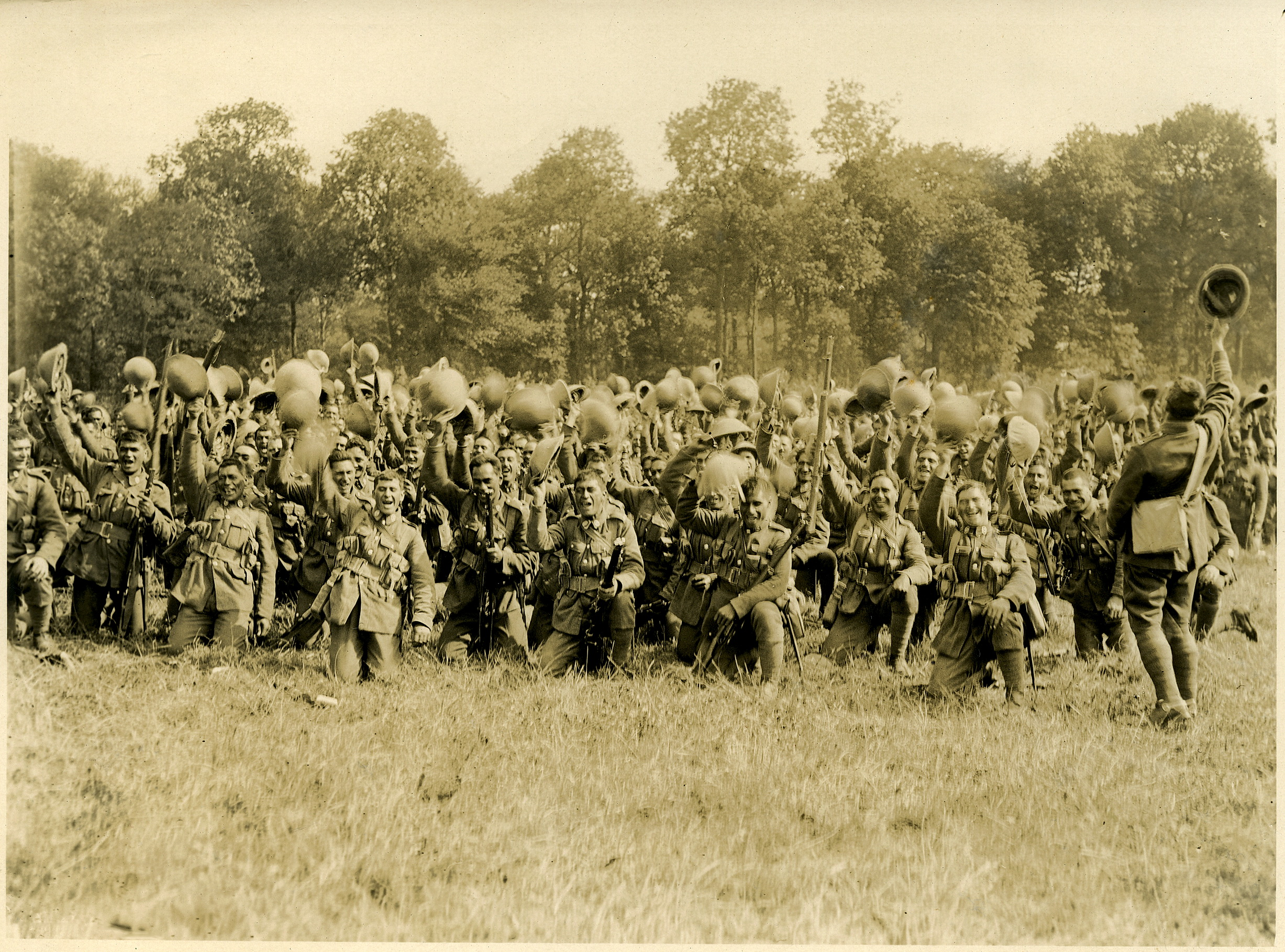 Members of the Maori Pioneer Battalion give a rousing farewell to visiting Prime Minister William Massey and Deputy Prime Minister Sir Joseph Ward who were departing after reviewing the troops. The photograph was taken at Bois-de-Warnimont, France on June 30, 1918, by the Official NZEF photographer, Henry Armytage Sanders. Henry Armytage Sanders was an Official NZEF Photographer (service number 37194) appointed by the New Zealand Government according to New Zealand Division documents. From Archives New Zealand Reference: IA76/13, H687.