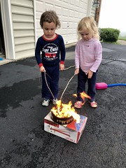 "The twins gather around a ""hobo fire"" on the driveway today"