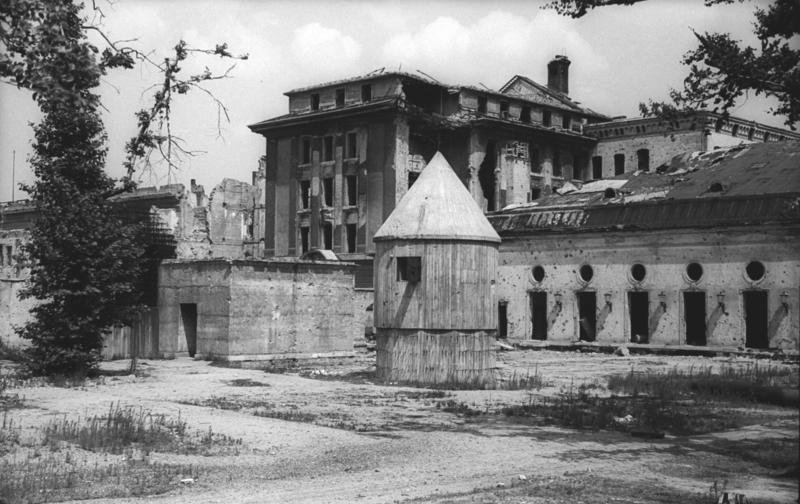 The above-ground portion of the Führerbunker photographed in July 1947. Hitler & Eva Braun's remains were burnt in a shell crater in front of the emergency exit at the left. The circular structure was for generators and ventilation