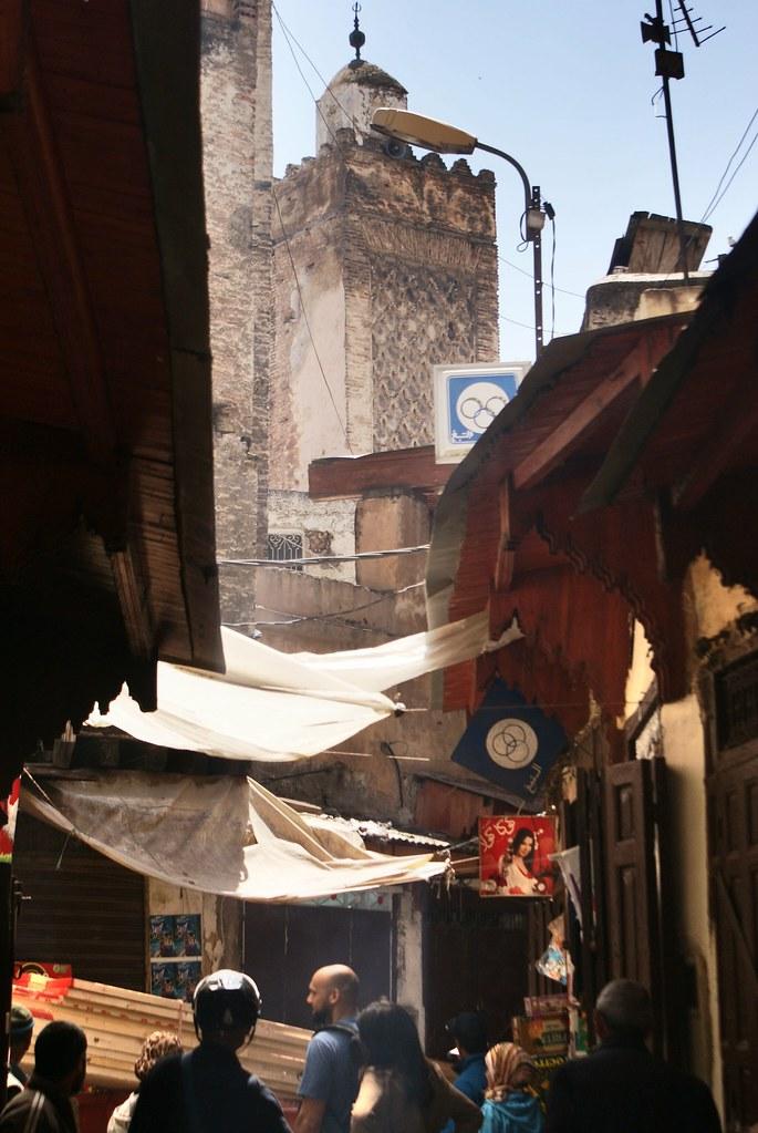 Ruelle de la Médina de Fès avec une tour monumentale au bout.