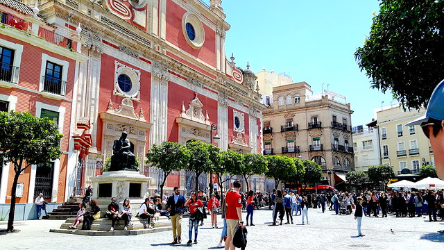 A colourful church and statue in a plaza in Seville, Spain with people milling about