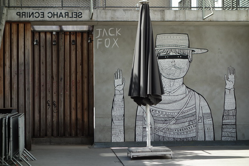 a backyard of a modern building, done in concrete, with a large street art poster of a human with a hat, a beard and a textured pullover
