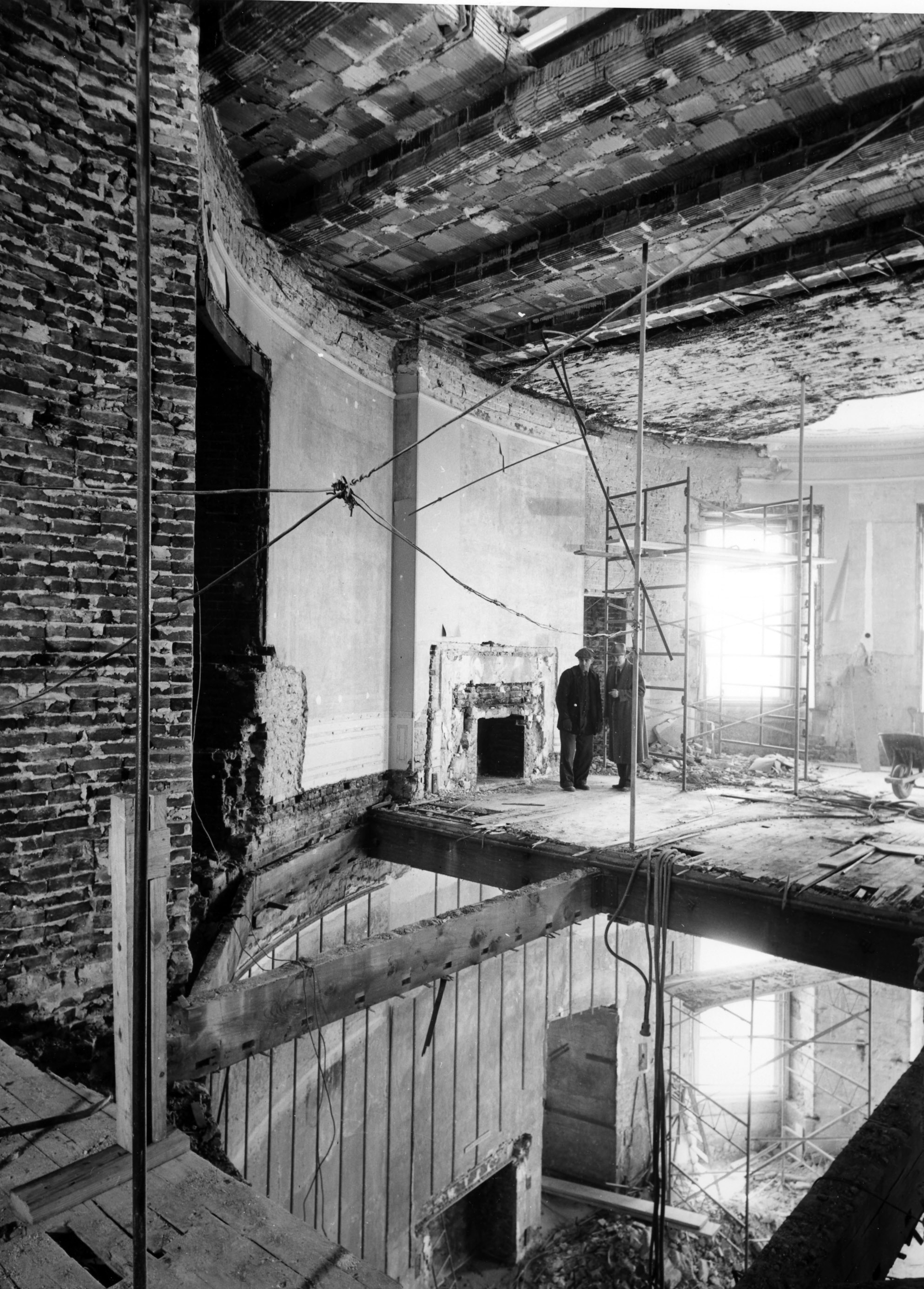 Two unidentified men stand in what remains of the second floor Oval Study above the Blue Room on March 9, 1950. The north wall and part of the floor have been removed for the installation of steel shoring columns. Photo from the holdings of the National Archives and Records Administration, cataloged under the National Archives Identifier (NAID) 6982095.