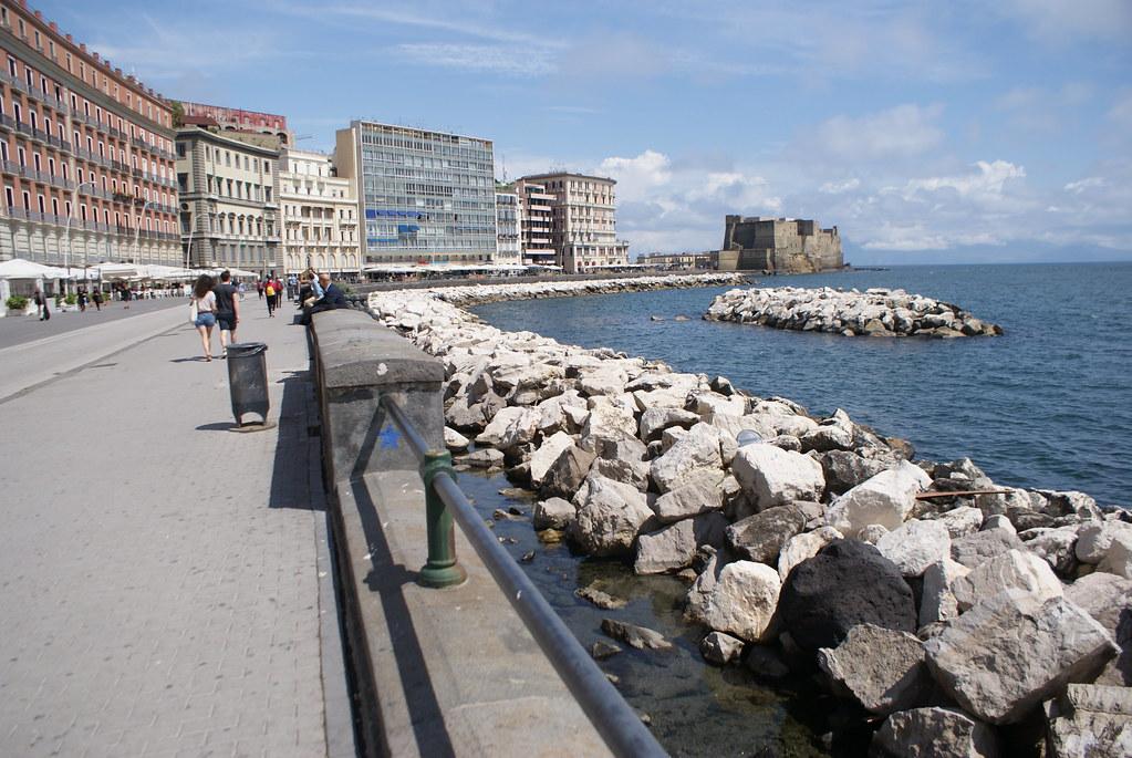 Via Partenope dans le quartier de Chiaia à Naples : Terrasses de restaurants et de cafés, grands hôtels avec vue sur le castel d'Ovo et la baie.
