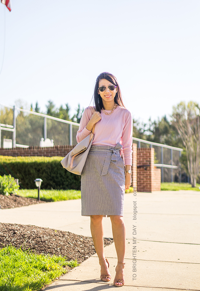 pink sweater, seersucker paperbag pencil skirt with bow tie, beige and gray tote, gold watch, brown sandals with knot detail