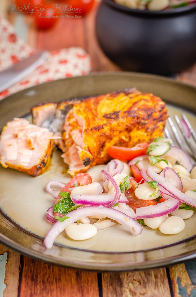 A plate of Peruvian lima beans salad served with salmon.  It is a simple salad tossed in a lime vinaigrette and great side dish.