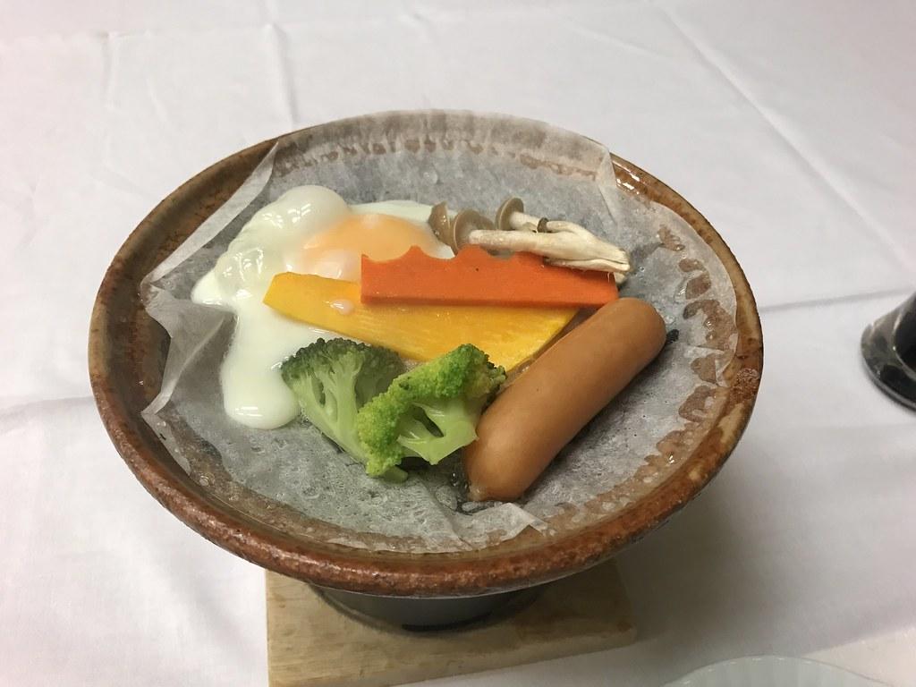 朝食サービスの目玉焼きと野菜の陶板