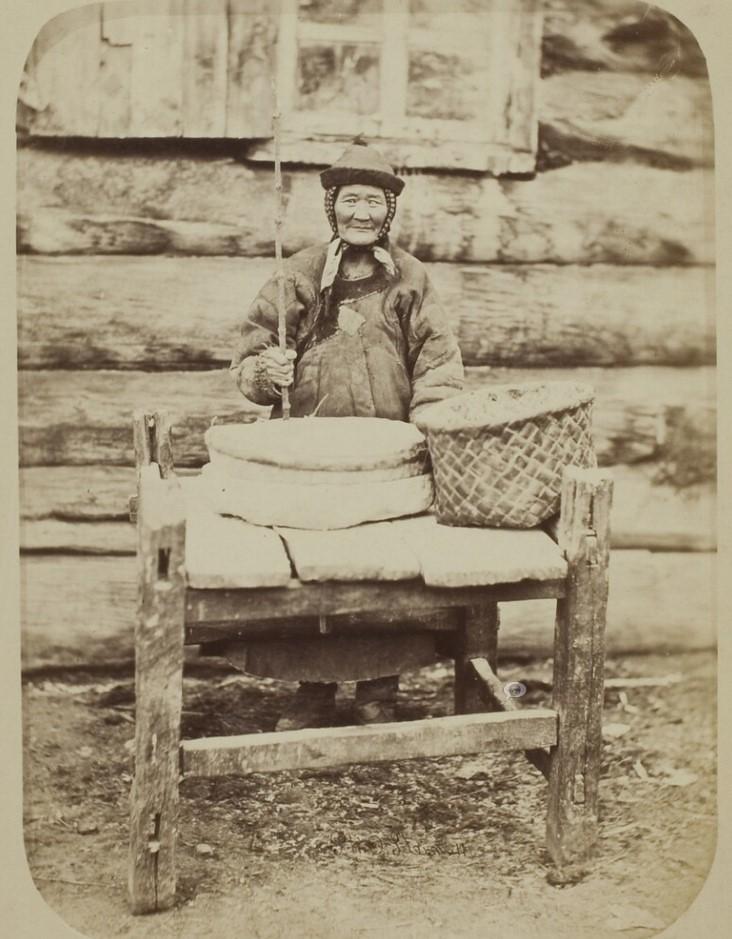 Бурятская женщина готовит муку на ручной мельнице