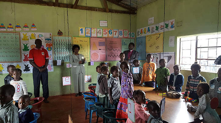 Jenny, Bishop Derek, teachers & young students greeting us at ECD Center, Fikola, Zambia