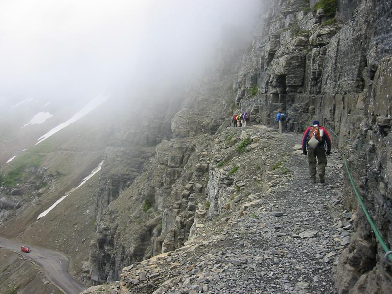 A group of hikers follows the Garden Wall section of the Highline Trail, just north of the Logan Pass visitor center. The fog is from a low-lying cloud in the valley. A red