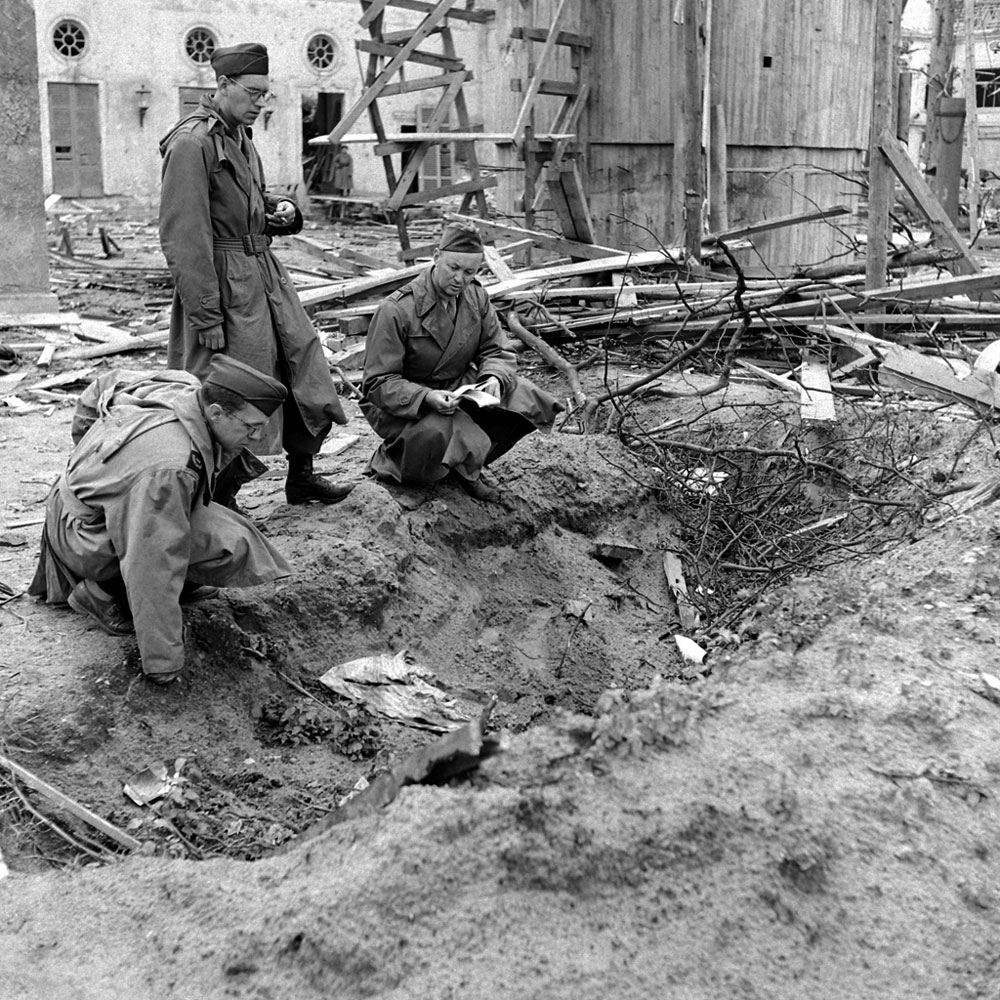 LIFE magazine correspondent Percy Knauth, left, sifts through debris in the shallow trench in the garden of the Reich Chancellery where, Knauth was told, the bodies of Hitler and Eva Braun were burned after their suicides.