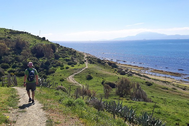A man hiking in Tarifa along the Mediterranean with a view across to Africa - one of the best things to do in Tarifa