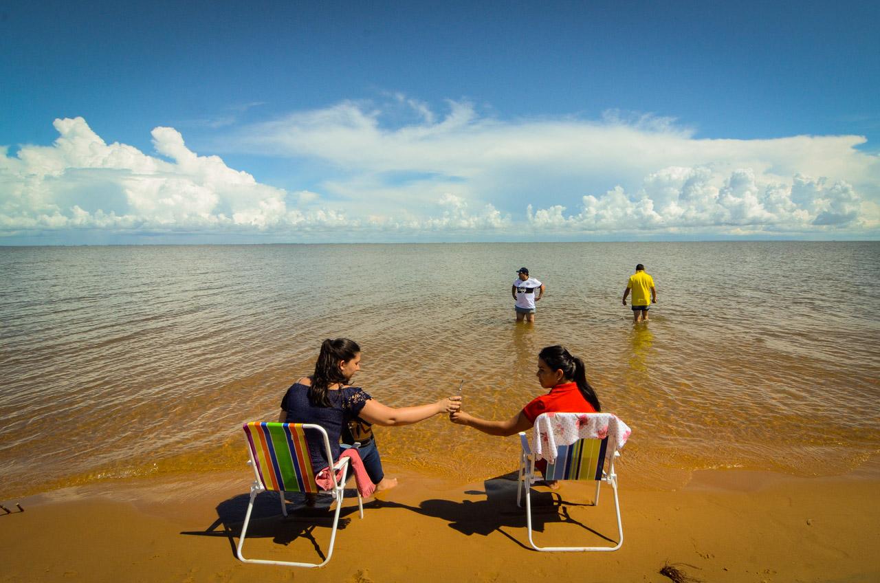 Dos mujeres comparten tereré en la playa de las dunas de San Cosme, mientras que sus parejas disfrutan del agua del río Paraná. Estar en las playas de las dunas de San Cosme es una experiencia similar a las playas del mar, por la brisa y las olas. Debido a la curvatura de la tierra, pareciera que el río y el cielo se funden en el infinito. (Elton Núñez).