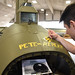"Museum restoration specialist Casey Simmons paints ""Pete and Repeat"" on the tail-gun position of the Boeing B-17F ""Memphis Belle"" during the restoration process, Jan. 30, 2018. Staff Sgt. John Quinlan, the tail gunner of the ""Memphis Belle"" crew, named the guns during World War II. Quinlan also received credit for shooting down one German fighter which is represented by the swastika. (U.S. Air Force photo by Ken LaRock)"