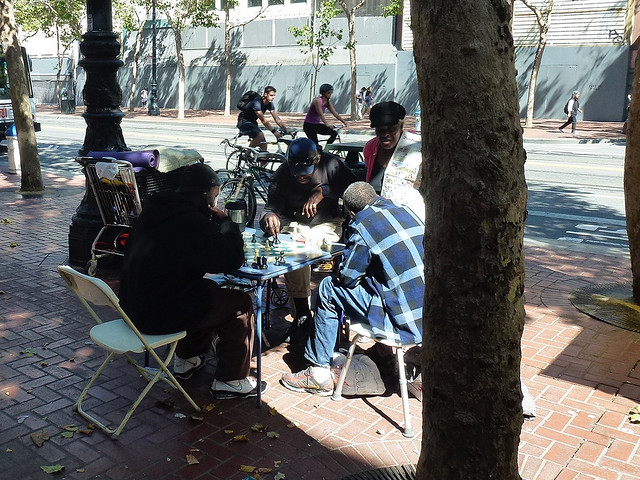 Homeless in San Francisco sitting around a table playing chess