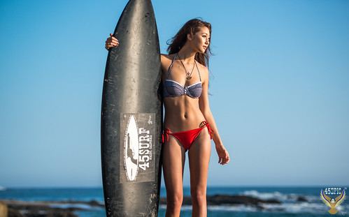 Black 45SURF Surfboard with Trademark Brand Logo! Pretty Asian Bikini Swimsuit Model! 45EPIC Sexy Hot Fitness Abs! Birth of Venus!  Tall, Thin, Fit Fitness Model! Surf's Up Beautiful Blue Sky Beach Day & Crashing Waves dx4/dt=ic!