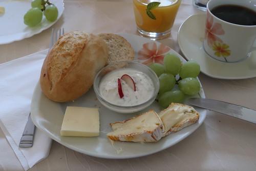 Weißes Brötchen mit Kräuterquark, Käse und Weintrauben