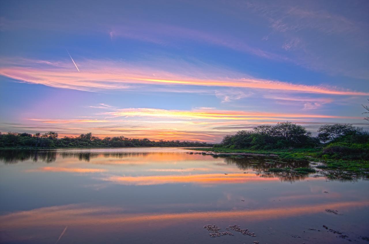 El sol se oculta en el horizonte chaqueño, revelando sus últimos haces de colores antes de desaparecer por completo. En la fotografía de larga exposición se filtra la traza que dejó un avión en vuelo. (Elton Núñez).