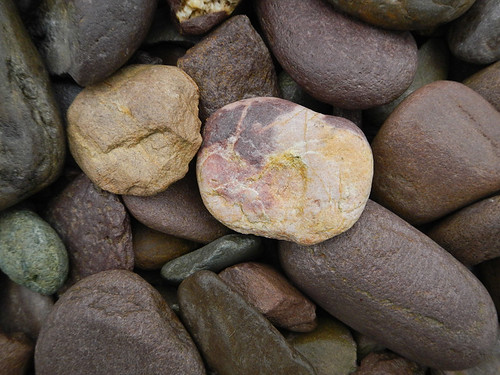 Purple-red stones dominate the beach at Rossbeigh Beach in Ireland